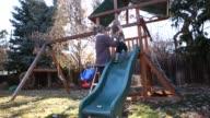17 month old toddler boy sliding down slide in backyard