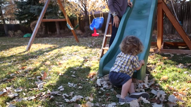 17 month old toddler boy sliding down slide in backyard
