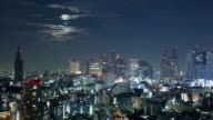 WS T/L Moon setting over Shinjuku business and entertainment area / Tokyo, Japan