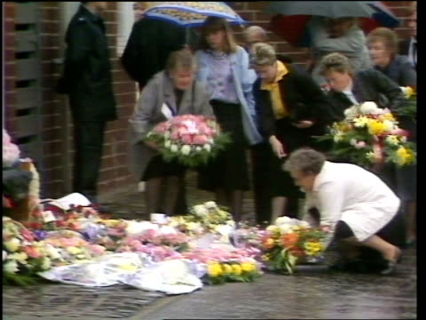 Pauline Reade Funeral ENGLAND Manchester Gorton Mourners line up to give wreaths put them on ground outside house MS SIDE Pauline's mother Joan...
