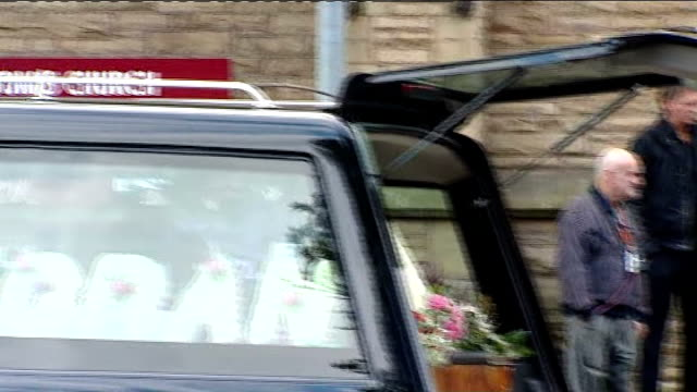 Winnie Johnson funeral Congregation arriving at church / hearse outside church / Bishop emerges from church / coffin carried into church / wreathes...