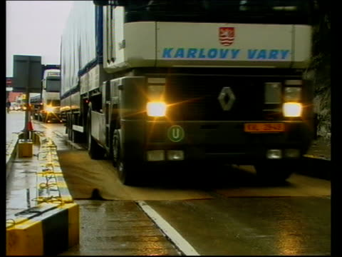 Spreads to continent ITN Lorries driving over disinfectant mats at port Sign by road side 'Slow Foot and Mouth Disinfection Point' as lorry past