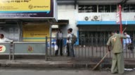 Morning commuters get into a taxi cab outside Churchgate suburban train station pan man rushing into station in Mumbai India on Thursday Dec 5...