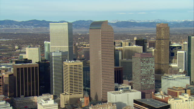 WS PAN Morning orbiting shot of Denver main downtown buildings with rocky mountains behind / Denver, Colorado, USA