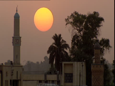 Mosque and trees against sky at sunset / Baghdad Iraq