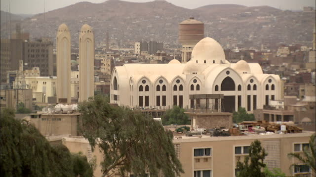 A mosque stands out against houses in the city of Aswan Egypt.\n Available in HD.