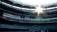Mostly empty Yankee Stadium ballpark blue seats some unidentifiable workers cleaning frieze roof top frame BRIGHT sun light glare coming through roof...