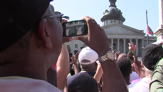 Mostly positive reactions but also negative a man holds up a Confederate flag amongst crowd