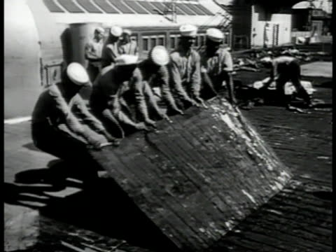 Mothballed air carrier in dock MS Sailors ripping off old floor tile on deck VS Sailors lifting covering of deck cannons rotating guns Korean War