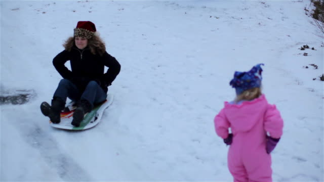 Mother acts silly as she snow sleds past her young daughter