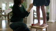 Mother altering a dress on her daughter