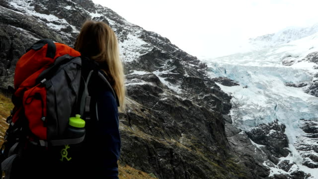 Mother and adult daughter hike below glaciated mountain face