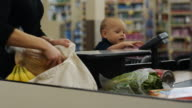 mother and baby at grocery store check-out