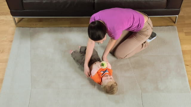 WS Mother and baby boy (6-11 months) playing on carpet / London, UK