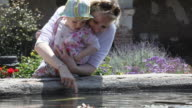 MS Mother and baby daughter (12-17 months) looking at fountain, San Juan Capistrano, California, USA