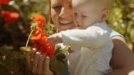 Mother and Baby girl outdoors looking at flowers