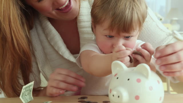 CU Mother and baby girl (12-23 months) putting coins into piggy bank / Jersey City, New Jersey, USA