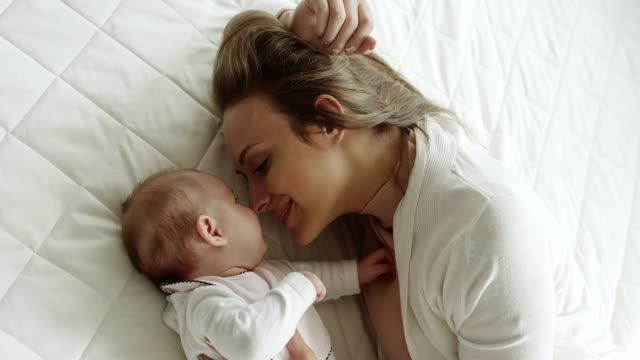 Mother and baby kissing like eskimos with their noses on bed
