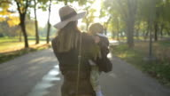 Mother and child walking together in autumn park