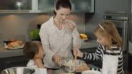 MS Mother and children (4-11) baking, girl stirring dough / Kleinmachnow, Brandenburg, Germany