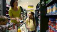 Mother and children shopping in supermarket