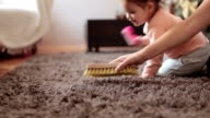 Mother and cute baby girl brushing the rug , baby is learning how to clean and assist her mother