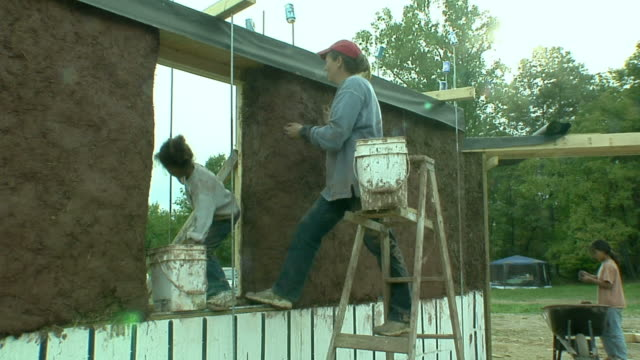 WS ZI MS Mother and daughter (4-5) applying adobe mud mixture to the walls of a straw house under construction, Grass Lake, Michigan, USA