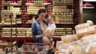 Mother and daughter buying bread in grocery store
