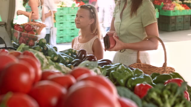 Mother and daughter buying produce at marketplace