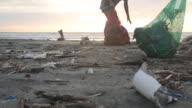 Mother and daughter collect garbage on beach, sunrise