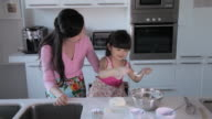MS Mother and daughter cooking together in kitchen / China