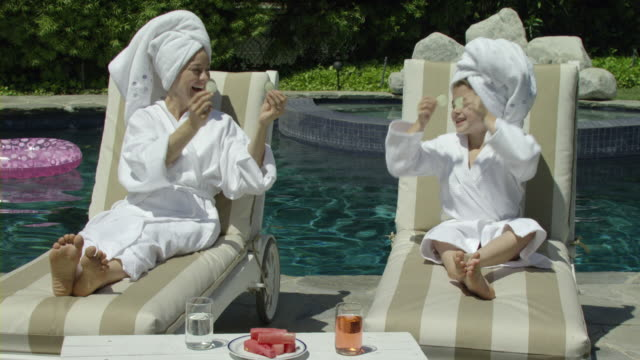 MS TU mother and daughter (8-9) covering eyes with cucumber slices sitting on deck chairs by pool, Encino, California, USA