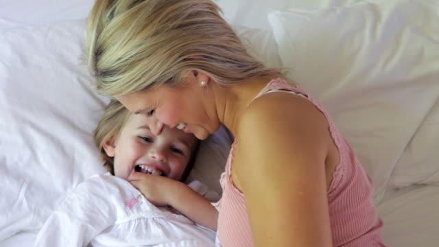Madre e figlia a letto Cuddling