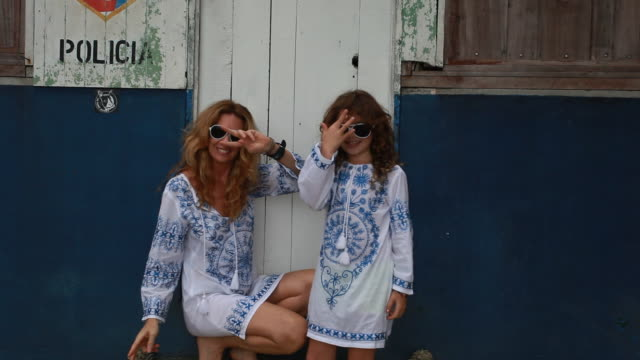 Mother and daughter doing goofy dance and with matching sunglasses and outfits then throw sunglasses and hug.