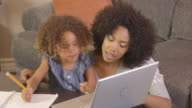 mother and daughter doing homework with laptop
