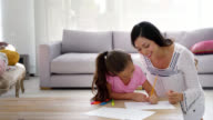 Mother and daughter drawing at home