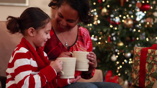 MS TU Mother and daughter (6-7) drinking hot cocoa at Christmas / Lamy, New Mexico, USA