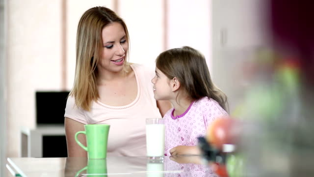 Mother and daughter drinking milk and coffee
