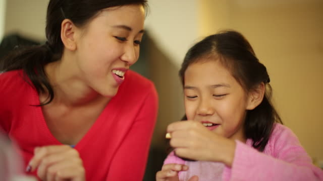 CU Mother and daughter eating cookies in kitchen