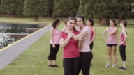 Mother and daughter embracing after run for breast cancer awareness
