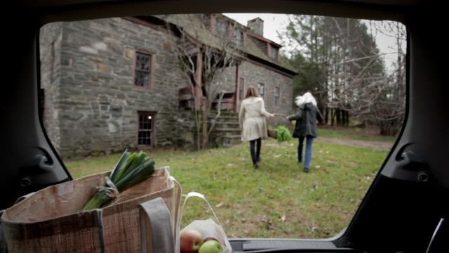 WS Mother and daughter getting groceries out of trunk of car / Kingston, New York, USA