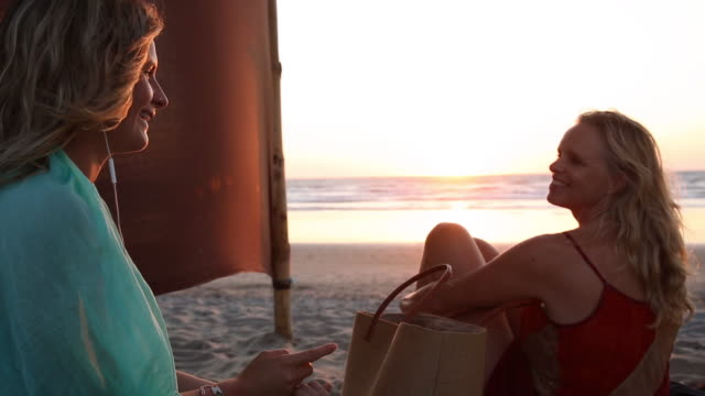 Mother and daughter have conversation on beach,