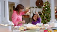 Mother and daughter have fun sprinkling flour on cookie dough in the kitchen (dolly-shot)