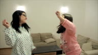 Mother and daughter have pajamas party at home