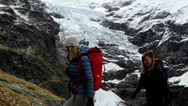 Mother and daughter hikers walk by a mountain stream at the foot of a glacier