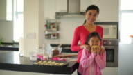 MS Mother and daughter in kitchen holding cookies