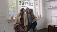 WS SLO MO. Mother and daughter kiss father on cheek and smile at camera in family owned business.