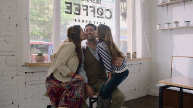 WS SLO MO. Mother and daughter kiss father on cheek in family owned neighborhood coffee shop.