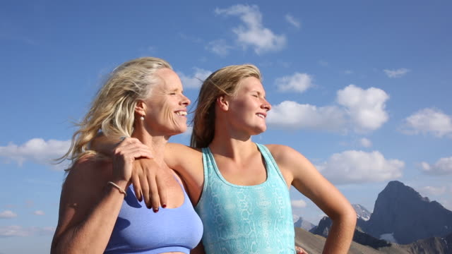 Mother and daughter look off from mountain summit, exhilarated