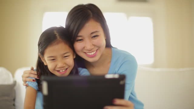 CU Mother and daughter looking at digital tablet.